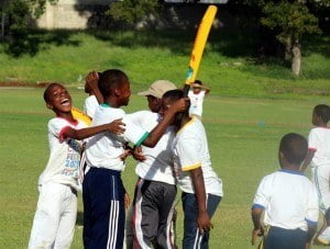Eden Lodge Primary's Raheem Holder (bat raised) is surrounded by his thrilled teammates after the team won the finals of the Scotiabank Kiddy Cricket Festival.