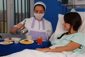 An employee of Ibero Caribe pours tea for a patient in hospital