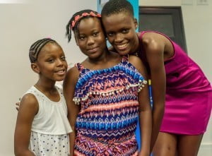Kittisha Doyle, winner of the recently-concluded Caribbean's Next Top Model (CNTM) Cycle 2, poses with two young fans during an autograph session at Flow's retail store in Sheraton Mall.