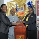 Adena Vaughn, Acting Branch Manager for CIBC FirstCaribbean Speightstown (left) and Michelle Whitelaw, Director Retail Banking Channels (right), accepts the commemorative Broken Trident from long standing customer Rupert Springer