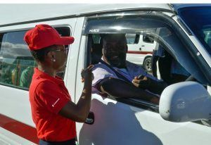 Scotiabank Wildey staffer Shannon Hunte shares a laugh with the driver of a Gall Hill ZR van after paying the fares for the entire van-load of passengers.