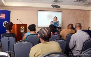 Deputy Chief of the U.S. Mission to Barbados, the Eastern Caribbean, and the OECS, Laura Griesmer (standing) delivers remarks to participants at the U.S. Embassy's interactive program to prevent LGBTI hate crimes.
