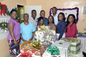 Members of CIBC FirstCaribbean Oistins branch pose with the Mother-in-Charge of the home just after presenting the hampers...