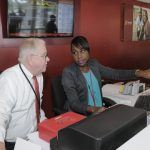 Customer Service Officer of CIBC FirstCaribbean, Tamesha Goddard trains new teller, Chief Executive Officer Gary Brown