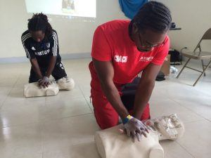 Coaches Barry Bourne (back) and Zico Callender going through the steps of administering CPR.