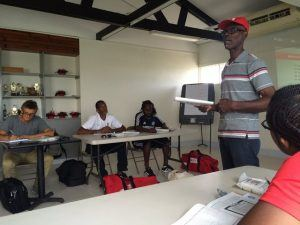 Instructor Lawrence Marshall of the Barbados Red Cross explaining first aid procedures to the coaches. Sitting at left is KickStart Director of Coaching David Porter.