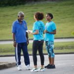 Members of Fortress Fund Managers' Random Acts of Fitness team chat with a walker in the car park of the Garfield Sobers Sports Complex to promote the Fortress Half Marathon