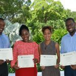 Four returning Chevening scholars with their certi 1