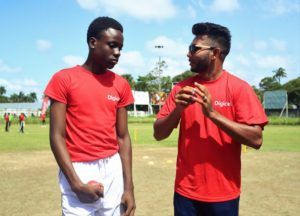 Devendra Bishoo shows a student from West Demerara Secondary School how to grip the ball