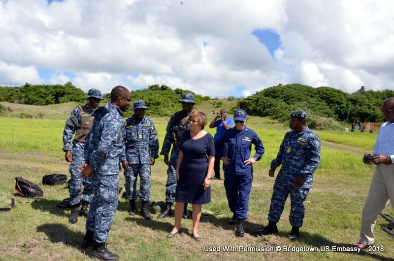 U.S. Ambassador to Barbados, the Eastern Caribbean, and the OECS, Linda Taglialatela (center) Commander Elizabeth Booker, Senior Defense Official/Defense Attaché, speak with police and military members from the region during the Marine Forces-South ten- day marksmanship instruction course