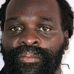 Jones is approximately 5 feet 5 inches tall, with a dark complexion, and slim build. He has a receding hairline and has Rasta locks. He has average eyes, a short broad nose, average ears and thick lips with a pink discoloration. He also has teeth missing from his lower jaw.