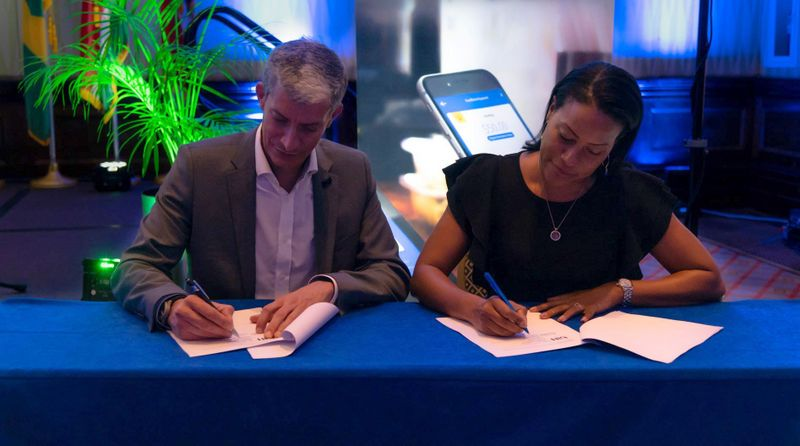(L to R) Rawdon Adams, Bitt's CEO and Efia Luis, COO of IBIS Management Associates Inc sign an MOU that could potentially benefit IBIS' commercial bank clients