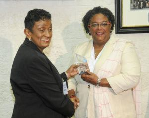 "CCRIF Deputy Chairperson, Mrs. Desirée Cherebin presents a ""payout memento"" to Prime Minister Mia Amor Mottley, recognizing the payout of US$5.8 million to the Government of Barbados after Tropical Storm Kirk."
