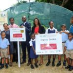 Here are the children who are working on the project pose in front of the green house with adults - Debra King – Head of Corporate Communications at CIBC FCIB; Principal George Francis; David Bynoe of GEF/SGP; Marsha Clarke of YEA and Dominique Jordan the teacher who manages the project