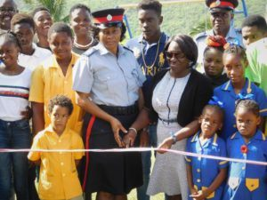 Principal of the St Elizabeth Primary School along with S/Sgt Christa Graham of the District F/Belleplaine Police Station flanked by student of the St. Elizabeth Primary School, Members of the Team and other police officers as they prepare to cut the ribbon to signal the reopening of the park.