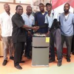 CaribSupply truck drivers Michael Miller and Dennis Turton handover donated refrigerator to members of the QEH Orderlies Departments