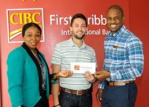 Grand Prize Winner Jomo Lashley (centre) receives his prize from Malcolm Martindale CIBC FirstCaribbean Warrens Branch Manager and Jennifer Fuller, Associate Director - Cards Issuing, Sales & Portfolio Management