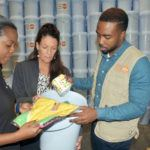 Harris Paints' Distribution Manager Raquel Graham and Product and Trade Marketing Manager Tracy Johnson of Harris Paints with U United Nations Population Fund (UNFPA) Programme Clerk Randy Warner look at some the items in the UNFPA dignity kits. These kits are stored at Harris Paints in Barbados before being sent to the National Office of Disaster Services (NODS) in Antigua and Barbuda where they can be distributed throughout the region.