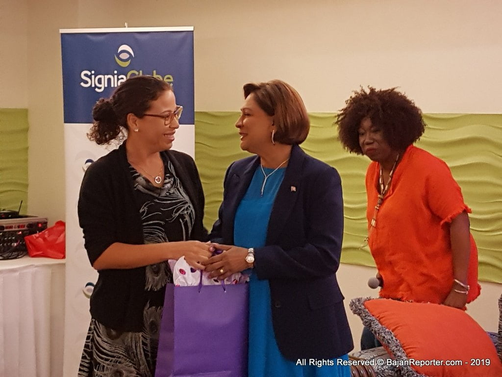 Shelly Ann DaSilva-Hee Chung (left), director of the American Chamber of Commerce Barbados & Eastern Caribbean (AmCham BEC) presents gift token for Kamla Persad-Bissessar, Opposition Leader of Trinidad and Tobago