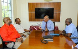Getting to know you: CIBC FirstCaribbean International Bank's Managing Director of Retail and Business Banking Mark St. Hill, second from right, speaking with, from left, beneficiary, Aldrin Jordan, his mentor, Michael Stuart and Credit Manager of The Cherry Tree Trust, Ezlon Griffith.