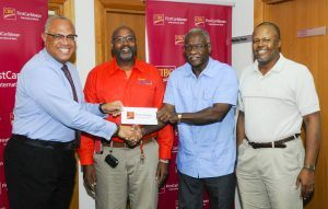CIBC FirstCaribbean International Bank's Managing Director of Retail and Business Banking Mark St. Hill, presenting Credit Manager of The Cherry Tree Trust, Ezlon Griffith, with the cheque for the fourth tranche of money under a five-year memorandum. Also pictured are beneficiary, Aldrin Jordan, second from left and his business mentor, Michael Stuart.
