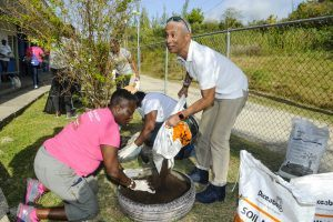 Michelle Whitelaw, Director of Retail levels the soil as Legal Counsel Brian Clarke pours Soil Mix into one of the tyres