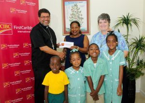 (from left) Roman Catholic Archbishop Dr. Jason Gordon receiving the sponsorship cheque from Debra King, CIBC FirstCaribbean's Director of Corporate Communications. Also pictured is headmistress, Sister Pauline Dempsey and pupils from the St. Patrick School