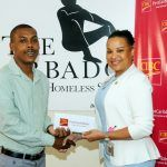 Donna Wellington (with a very rare smile, from the eyes down only) Managing Director for Barbados presents the cheque to Head of BVHS, Kemar Saffrey