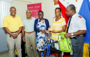 Parent, Ms. Dionne Drakes, fourth from left receiving a voucher from Trustee of FirstCaribbean International Bank Comtrust Foundation, Ms. Lynda Goodridge. Others pictured from left are Member of the Salvation Army's Advisory Board, Mr. Michael Stuart, Mr. Wilfred Field and the Salvation Army's Divisional Commander Major Darrell Wilkinson.