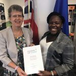 Alian Olivierre receiving Commonwealth Point of Light award from High Commissioner Janet Douglas