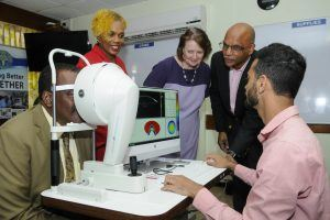 """(SEATED AT MACHINE AS PATIENT) <strong>Minister of Health and Wellness, Lt. Col. Jeffrey Bostic welcomed having the machine at the QEH. He said</strong>, """"As a public healthcare provider, the QEH is establishing centres of excellence in certain specialist areas of care, one of which is ophthalmology. I am pleased to state that the Department of Ophthalmology of the QEH is the only eye care facility of its kind within the Caribbean and has garnered a stellar reputation for the delivery of superior care to its patients. Presently, the department provides specialist care in paediatric, glaucoma, neurosurgical and ocuplastics care, which makes it the only eye care facility in the region to offer this range of specialised ophthalmic care and I think that this is something that we in this country should be very proud of..."""""""