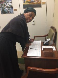 Gwendolyn Briley-Strand, world-renowned actress, pens a mark on the visitor's book at Senator Tom Carper Office (D-DE) in Washington, D.C.