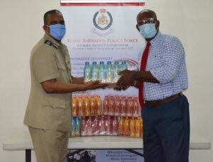 Deputy Commissioner of Police Mr. Erwin Boyce and Assistant Commissioner of Police Mr. Sylvester Louis accepting the donation of Lucozade on behalf of the Force.