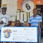 Mega 6 Jackpot winner Tyrone Harvey (2nd left) and his wife (seated) celebrate with their $385,000 cheque at B & D Variety. Also sharing in the celebration (left - right) Kibibi Cumberbatch, Brand Manager, The Barbados Lottery, DaCosta Lynch, B & D Variety owner and Barbados Lottery retail agent and Michelle Jones, Customer Service Coordinator, The Barbados Lottery.