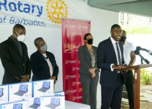 Mr. Raymond Ward of CIBC FirstCaribbean speaking at the ceremony while from left Senator Dr. Rommel Springer, Chief Education Officer (Ag) Ms. Joy Adamson, Ms. Fiona Hinds, Mr. Winston Warren of the Rotary Club look on