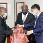 His Excellency, Ambassador Yan Xiusheng of the Republic of China presenting gifts to Ian Gooding-Edghill Minister of Transport Works and Water Resources. The Minister of Water Resources, Charles Griffith observes, as per normal.