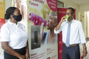 Principal of Lester Vaughn Secondary School, Anthony Alleyne, takes his first drink from the newly installed water station at the school as Alicia Jarvis of Newport Water looks on