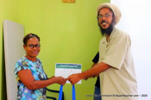 National Program Technical Officer of the Inter-American Institute for Cooperation on Agriculture (IICA), Mr. Damian Hinds, presenting certificate to deaf participant Waveney Reid-Davis