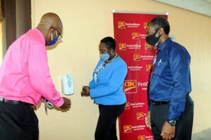 Michelle Whitelaw (Centre) tests the first dispenser installed at St. Elizabeth Primary School. (left) Principal of the School John Quinton and (left) Senior Teacher Richard Broome.