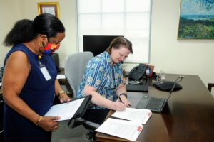 Chief Executive Officer of CIBC FirstCaribbean and Chair of its charitable arm, the FirstCaribbean ComTrust Foundation, Colette Delaney signs the MOU while Debra King, CIBC FirstCaribbean's Director of Corporate Communications and a Trustee of the Foundation assist.