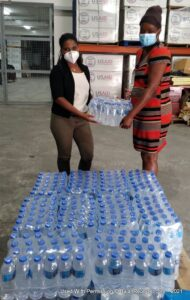 Camille Wiltshire, Curator of Global Shapers - Bridgetown Hub delivers water supplies to Ms. Daveda Chase, Storekeeper, Department of Emergency Management