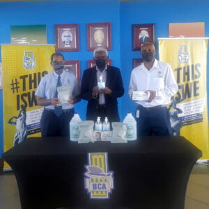 Dr. Roland Butcher, CEO along with Condé Riley, President (left to right) of the Barbados Cricket Association display some of the PPEs and sanitization products received from IGT Global Services and The Barbados Lottery, represented by Site Operations Manager Ferdinand Lord (right).