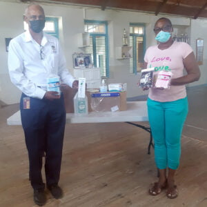 Ferdinand Lord, Site Operations Manager, The Barbados Lottery (left) presents Cheryl-Ann Forde, Secretary Treasurer, The Learning Centre with a donation of PPEs and sanitizers, recently.
