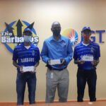 Mr. Ferdinand Lord, Site Operations Manager (centre) of The Barbados Lottery presents gift vouchers valued at $1,000 towards cricket supplies to Daniel and Darius Joseph.