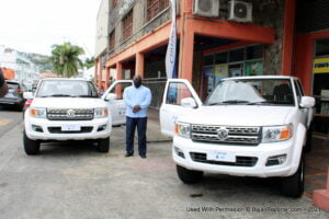 CEO of Coreas, Joel Providence stands with the two donated vehicles