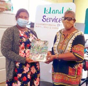 Patricia G. Turnbull (R), author of Ti Koko and Kush Kush, holding the storybook with bookseller Seema Omroa of Island Services, Ltd., Tortola. (P. Turnbull photo.)